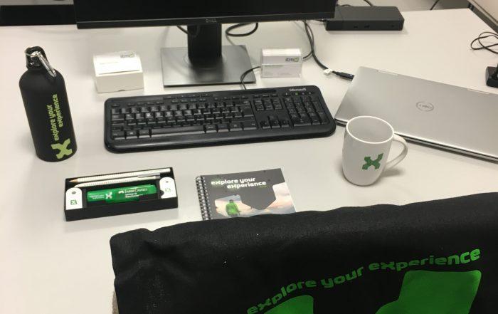Arbeitsplatz mit itmX Tasse, Block, Flasche und Tasche