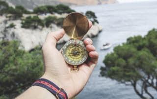 Hand die ein Kompass hält